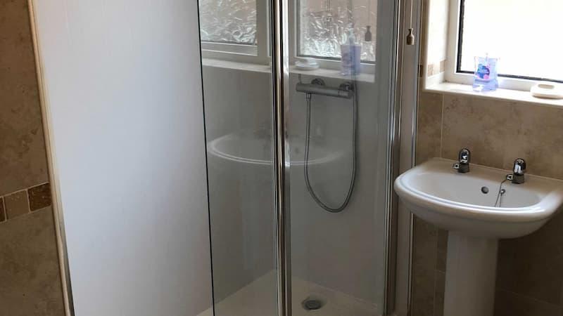 Walk in shower with glass slide door with window
