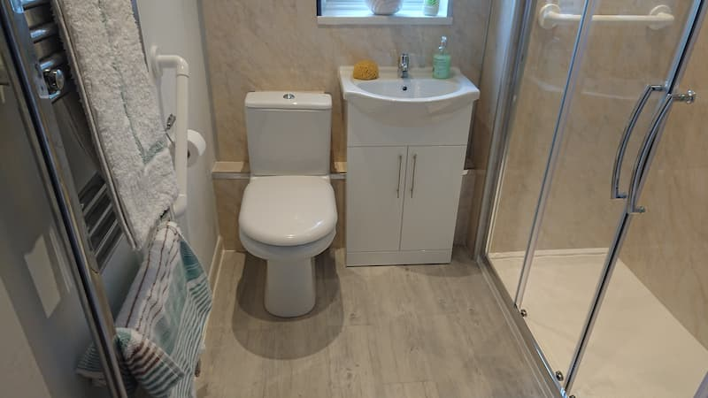 Grey bathroom with walk in shower toilet and sink