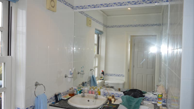 white and blue bathroom with large mirror, toilet and sink