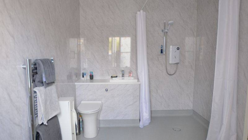 White Wet room with shower curtains and towel rack