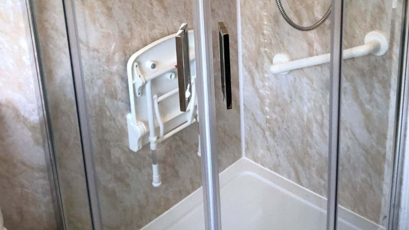 Clean walk in shower with handrail and seat